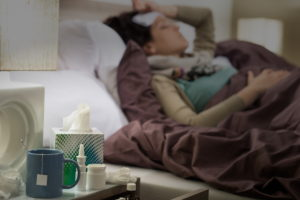 woman sick with flu laying in bed